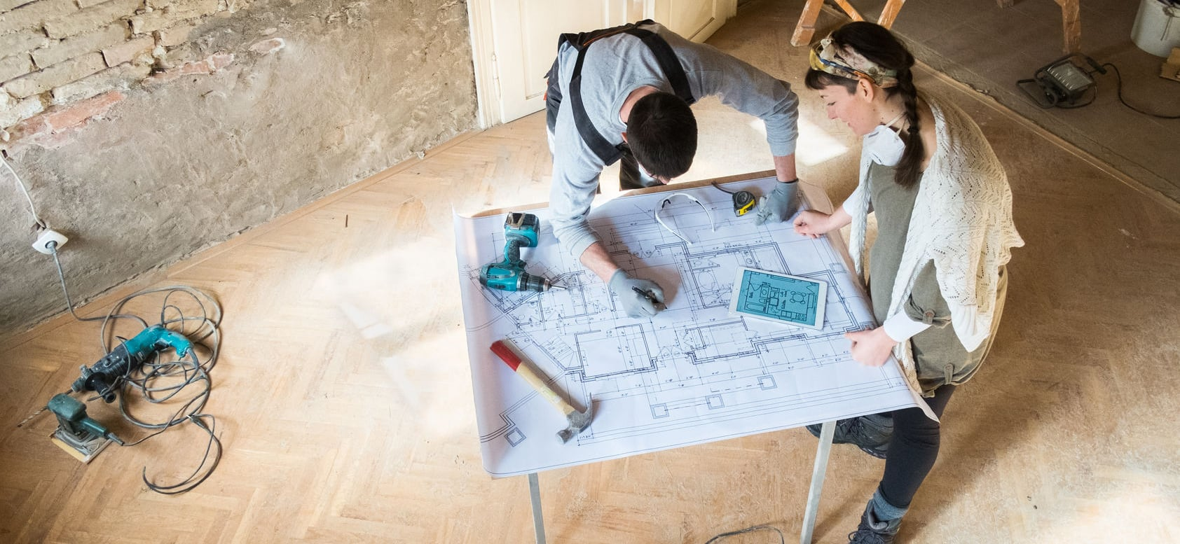 two persons drawing a floorplan